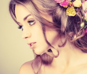 Beautiful girl with varicoloured flowers in hairs
