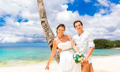 Happy groom and bride having fun on the sandy tropical beach. We