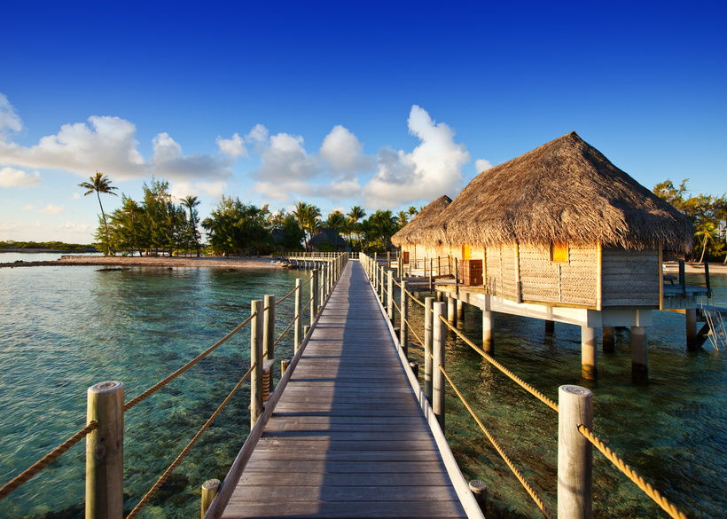 The wooden road over the sea to the tropical island.