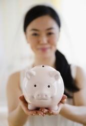 Japanese bride holding piggy bank