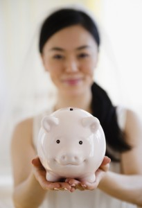 Japanese bride holding piggy bank
