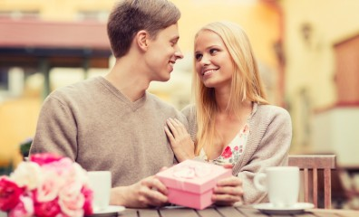 romantic happy couple with gift in the cafe