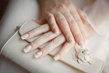 bride's arms with manicure holding a wedding purse