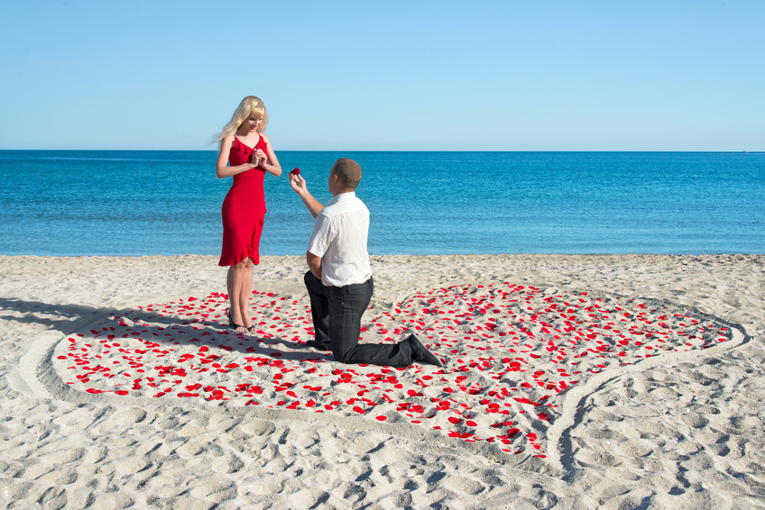 Loving couple on sea sandy beach - a man making proposal with gold ring to his pretty blonde woman in red dress in the heart of roses petals