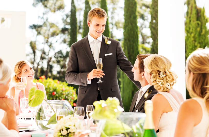 Young best man looking at newlywed couple while giving speech during reception. Horizontal shot.