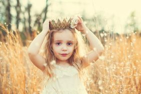 Beautiful outdoor natural light and a wreath around her head make this a stunning photo of a child in Charlotte NC.