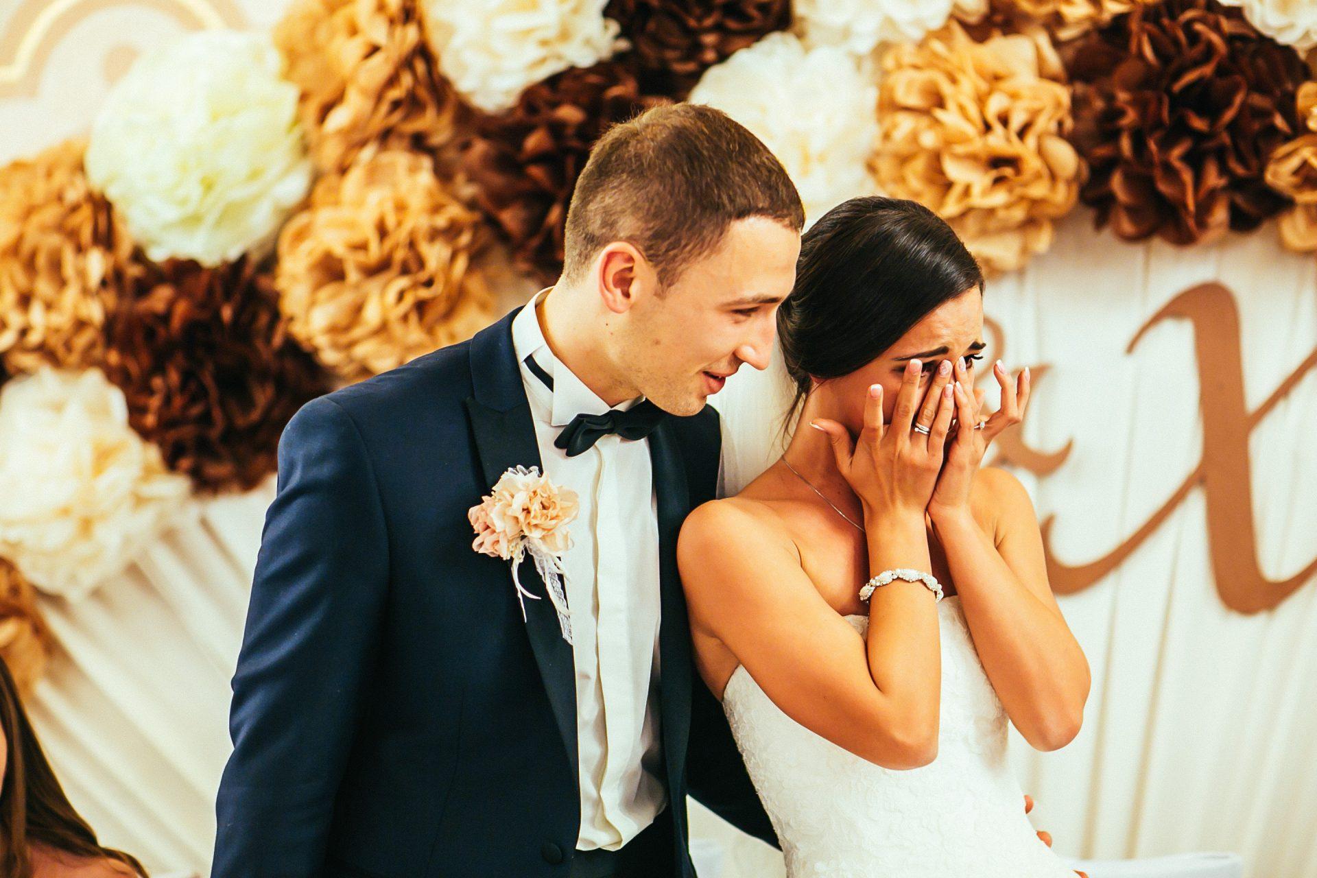 泣いている花嫁と支える新郎